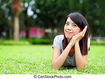 Asian woman lying on the grass
