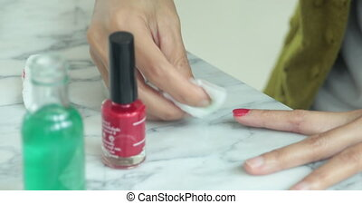 Asian woman make a beautician applying nail polish to female...
