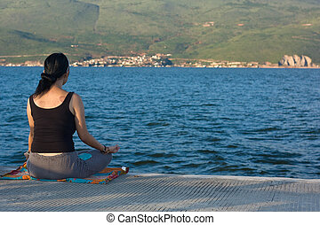 asian woman meditating next to lake