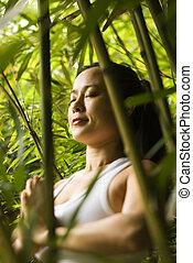 Asian woman meditating. - Portrait of Asian American woman...