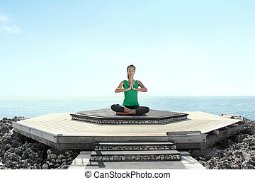 Asian woman on the beach doing meditation