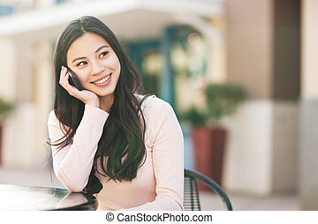 Asian woman on the phone - A shot of an asian woman talking...