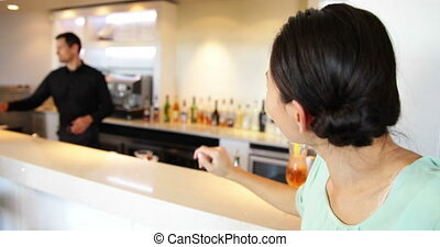 Asian woman ordering a cocktail from bartender at the local...