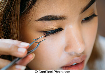 Asian woman placing decorative eyelashes on eye