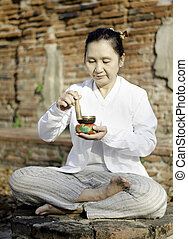 Asian woman playing a tibetan bowl, traditionally used to...