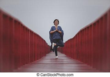 asian woman playing yoga pose on red wooden bridge