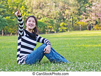 Asian woman pointing the tree