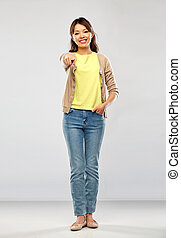 asian woman pointing to you over grey background