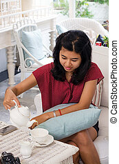 Asian woman pouring tea from the teapot