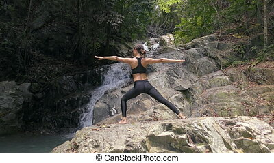 Asian Woman Practicing Yoga at the Waterfall