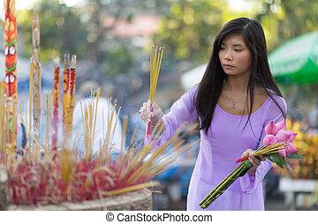 Asian woman praying at temple