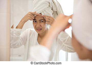 Asian woman pressing acne on her forehead