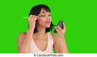 Asian woman putting on make-up against a green screen