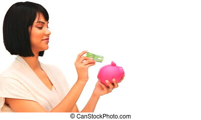 Asian woman putting on money in a piggy bank isolated on a...