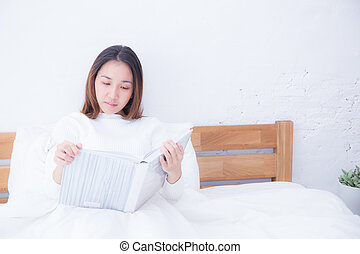 Asian woman reading a book and smiling in bedroom. lifestyle concept.