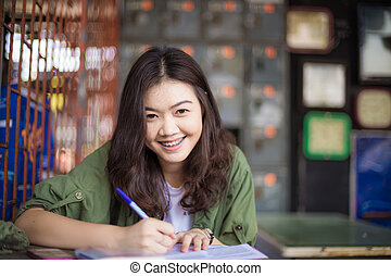 Asian woman reading a book while sitting on wooden table