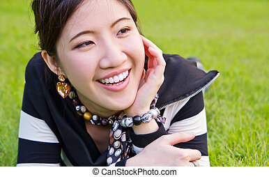 Asian woman relaxed on the grass