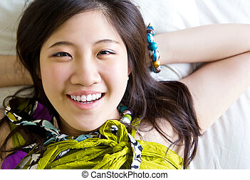 Asian woman relaxing on the bed