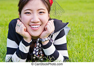 Asian woman relaxing on the grass