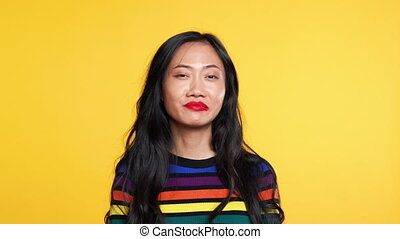Asian woman say yes and then say no on yellow background. ...