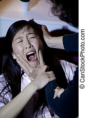 Asian woman screaming while man is abusing and hitting her -...