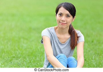 Asian woman setting on the grass