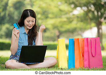asian woman shopping online with credit card
