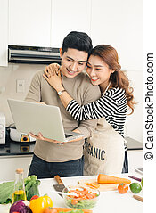 Asian woman showing something on the laptop to her boyfriend in the kitchen