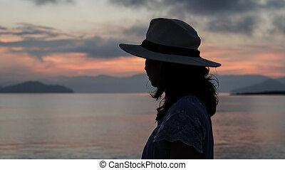 Asian woman silhouette at sunrise ocean pink and orange sky