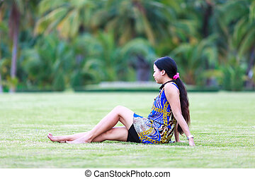 Asian woman sit on ground in park