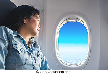 Asian Woman sitting at window seat in airplane and look outside window see blue sky and cloud ,traveling concept