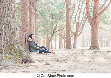 Asian woman sitting in the forest