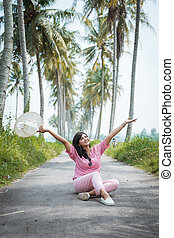woman sitting in the middle of country road with coconut trees