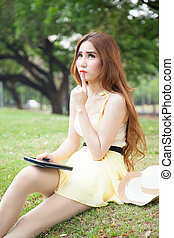 Asian woman sitting in the park and thinking.