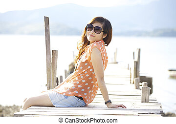 Asian woman sitting on bridge
