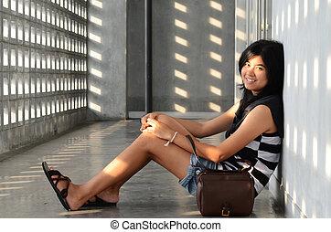 Asian woman sitting on corridor floor