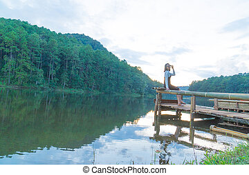 Asian woman sitting on raft.