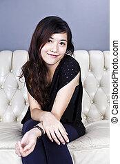 Asian woman sitting on sofa