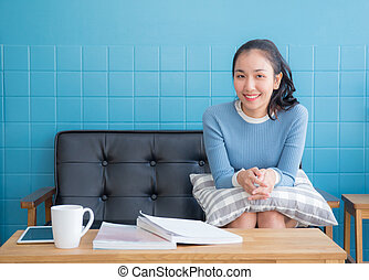 Asian woman sitting on sofa with pillow in the living room.