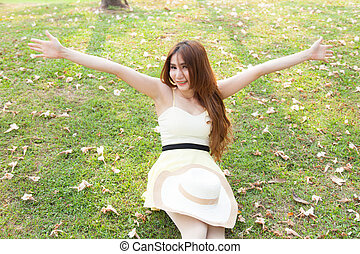 Asian woman sitting on the grass