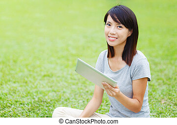 Asian woman sitting on the lawn with tablet
