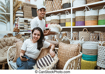 Asian woman sitting on the sofa holding cellphones and Asian man holding basket crafts