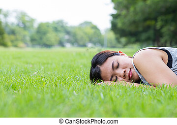 Asian woman sleeping on grass in the park
