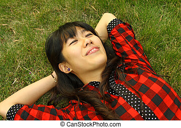 Asian woman sleeping on the grass and very relax