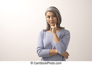 Asian woman smiling and pointing her finger to her cheek
