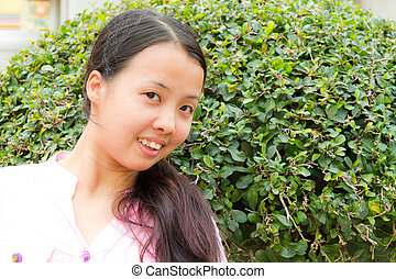 Asian woman smiling in front of tree