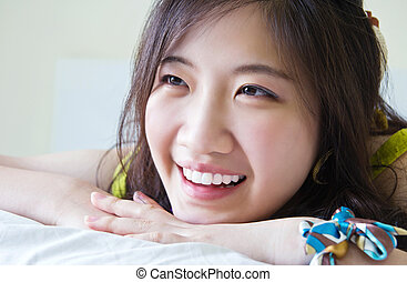 Asian woman smiling on the bed
