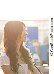 Asian woman smiling under sunlight