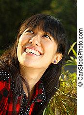 Asian woman smiling under sunshine
