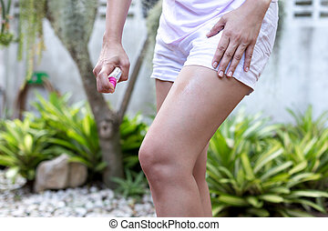 Asian woman spraying insect repellent on her leg